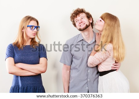 Jealousy and betrayal concept. Abandoned jealous girl watching on happy couple - young attractive blondie woman kissing handsome boy. - stock photo