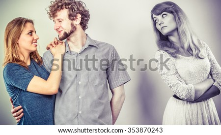 Jealousy and betrayal concept. Abandoned jealous girl watching on happy hugging couple. Triangle relationship. - stock photo