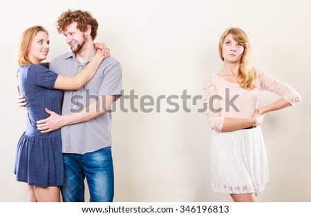 Jealousy and betrayal concept. Abandoned unloved girl watching on happy hugging couple. Triangle relationship. - stock photo