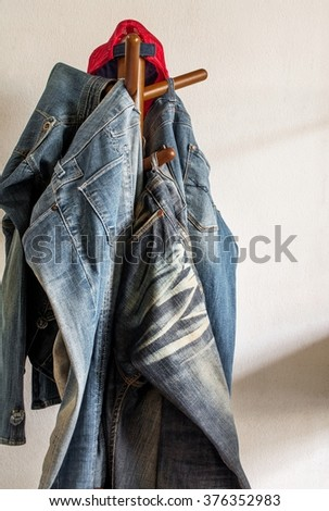 Jeans and cap hanger on wooden rack in front of a white wall and light from window. - stock photo
