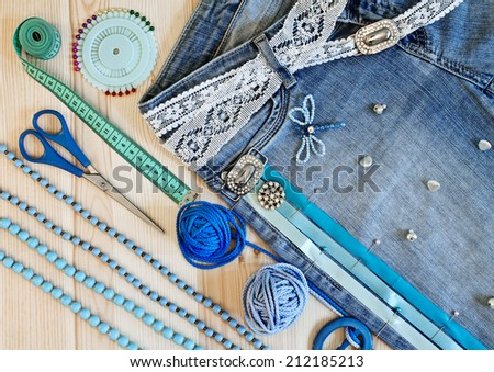 Jeans decorated with ribbons and lace by hand on a wooden background - stock photo