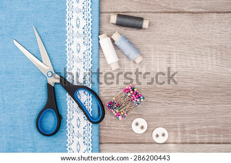 Jeans fabric for sewing, lace and accessories for needlework on old wooden background. Spool of thread, scissors, buttons, sewing supplies. Set for needlework top view - stock photo