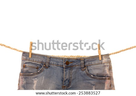 jeans hanging on a rope clothesline isolated on white - stock photo