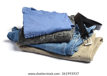 Jeans, pants, sweaters and t-shits with a belt folded on a white table - stock photo
