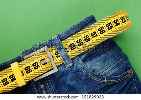 jeans with meter belt slimming on the green background - stock photo