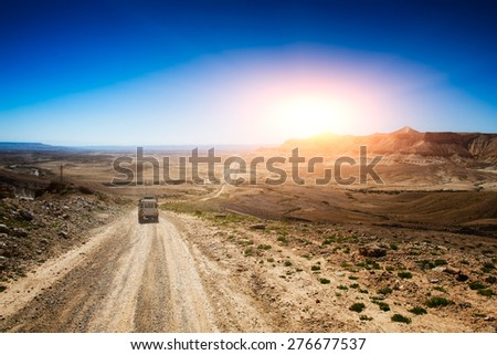 Jeep in a desert road - stock photo