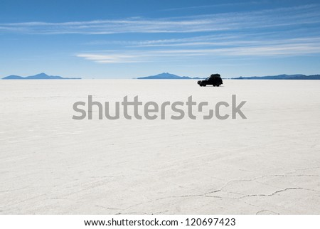 Jeep in the middle of salt desert Uyuni, Bolivia. - stock photo