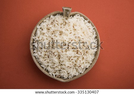 jeera rice, long-grain basmati rice flavoured with fried cumin seeds , served in a ceramic bowl, top view, isolated and top view on orange background - stock photo