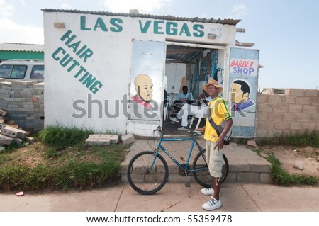 JEFFRE'YS BAY, EASTERN CAPE- MAY 15: life in the township  tokyo sexwhale , a southafrican fan of brasil in front of a typical hair cutting shop in a township, 15 may, 2010 jeffrey's bay, south africa - stock photo