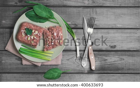 Jellied meat jelly on a green plate, young onions, spinach leaves on rustic vintage gray wooden background, top view, empty place for text, recipe - stock photo