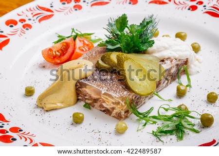 Jellied pork and beef with dill and parsley on the plate on a mustard background - stock photo