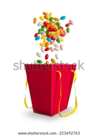 Jelly color beans falling in red paper bag isolated on white background - stock photo