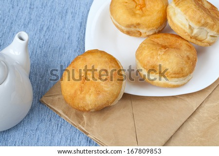 Jelly filled Bismark doughnuts on white plate over craft packet, ready to eat - stock photo