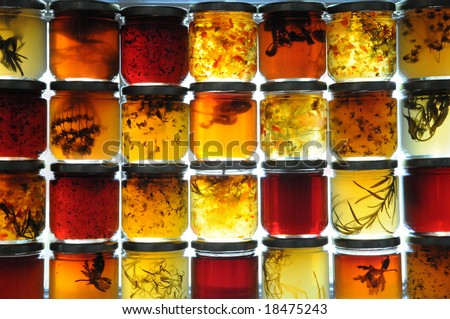 Jelly jars full of preserves sitting on window ledge backlit by sun. - stock photo