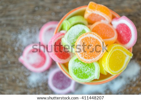 Jelly sweet, flavor fruit, candy dessert colorful in ceramic bowl on wood background. - stock photo