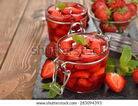 Jelly with strawberries in a glass jar on a brown background - stock photo