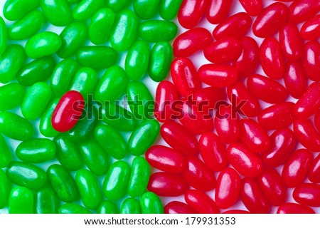 Jellybeans set into 2 halves of green and red with one red outsider on the green side. - stock photo