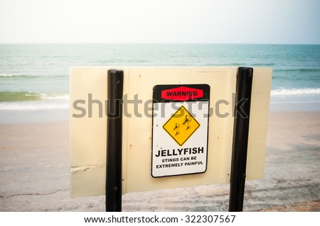 Jellyfish warning sign at summer beach. - stock photo
