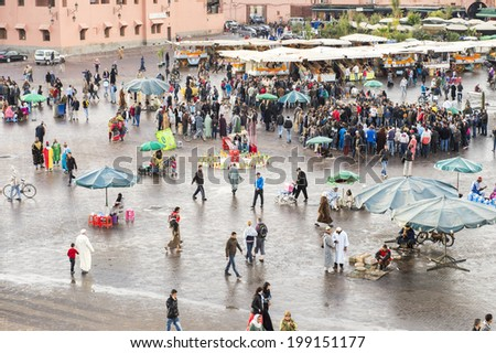JEMMA DAR FNA, THE MAIN BAZAAR, MARRAKECH, MOROCCO, MAY 11, 2014. People strolling around the booths and stalls in Jemma Dar Fna,  Marrakech, Morocco, on May 11th, 2014. - stock photo