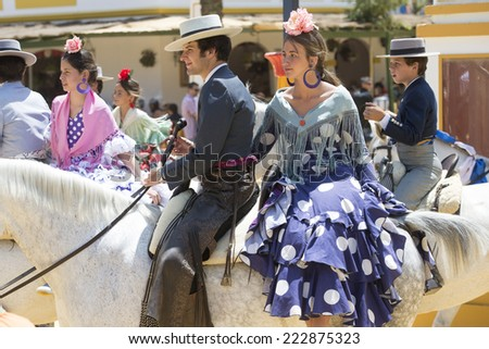 JEREZ DE LA FRONTERA, SPAIN-MAY 17: Couple mounted on horse and dressed in typical Andalusian costume, on fair ride on May 17, 2014 in Jerez de la frontera. - stock photo