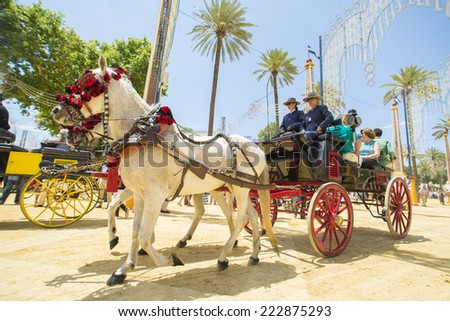 JEREZ DE LA FRONTERA, SPAIN-MAY 17: People mounted on a carriage horse, on fair ride on May 17, 2014 in Jerez de la frontera. - stock photo