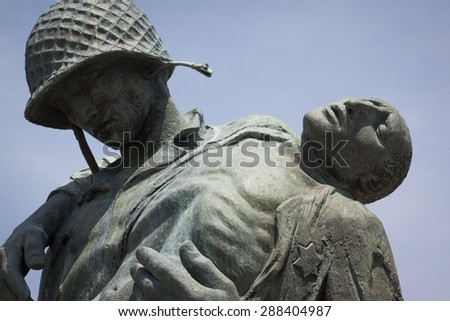 JERSEY CITY, NJ - MAY 26 2015: Close-up view of the Liberation Monument, a memorial to the Holocaust depicting a US soldier carrying a Nazi death camp survivor at Liberty State Park. - stock photo