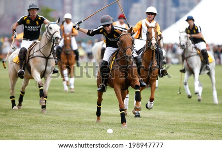 JERSEY CITY, NJ-MAY 31: Hilario Figueras (C) chases the ball during the polo match at the 7th Annual Veuve Cliquot Polo Classic at Liberty State Park on May 31, 2014 in Jersey City, NJ. - stock photo