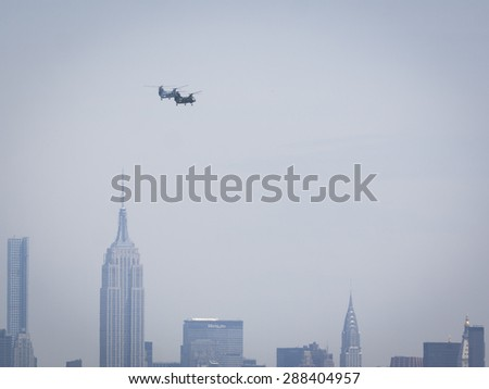JERSEY CITY, NJ - MAY 26 2015: US Marine Corps helicopters fly past the Empire State Building along the Upper New York Bay before the USS San Antonio departs Pier 92 at the end of Fleet Week NY 2015. - stock photo