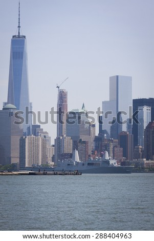JERSEY CITY, NJ - MAY 26 2015: USS San Antonio (LPD 17) passes the Freedom Tower at One World Trade Center on the Upper New York Bay after departing Pier 92 at the end of Fleet Week NY 2015. - stock photo