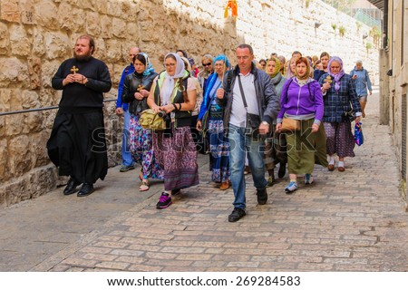JERUSALEM - APR 10, 2015: Pilgrims from all over the world commemorating the crucifixion of Jesus by carrying a cross along via dolorosa, on orthodox good Friday, in the old city of Jerusalem, Israel - stock photo