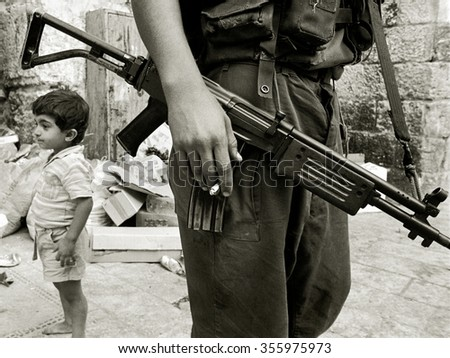 JERUSALEM, ISRAEL - August 22, 1987: An Israeli soldier armed with a Galil assault rifle patrols past a young Muslim Arab boy during the Intifada on August 22, 1987 in Jerusalem's Old City, Israel. - stock photo