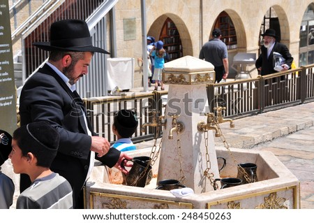 JERUSALEM, ISRAEL - CIRCA AUGUST 2014: Man performs ablutions before prayer at the Western Wall circa Augusy 2014 in Jerusalem, Israel. - stock photo