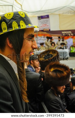 JERUSALEM, ISRAEL - FEBRUARY 25, 2016: A crowd and their Rabbi, part of a celebration of the Jewish Holyday Purim, in the ultra-orthodox neighborhood Mea Shearim, Jerusalem, Israel - stock photo