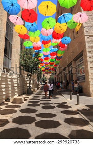 JERUSALEM,ISRAEL - JULY 19,2015:Colorful umbrellas floating magically in the sunny blue sky above pedestrian Yoel Moshe Salomon Street with galleries, ceramics, arts jewelry and clothing shops  - stock photo