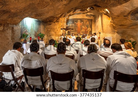 JERUSALEM, ISRAEL - JULY 13, 2014: Franciscan monks during mass in Grotto of Gethsemane - chapel located in cave near Tomb of the Virgin Mary. This is the place where Judas Iscariot betrayed Jesus. - stock photo