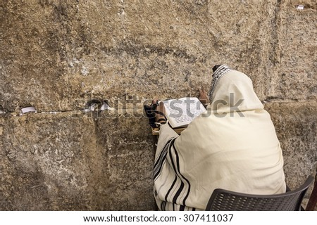 JERUSALEM, ISRAEL - JULY 16, 2015: Prayer prayes at Western Wall on Tisha B'Av - annual fast day in Judaism, commemorates anniversary of destruction of the First and Second Temples in Jerusalem. - stock photo