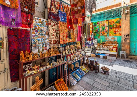 JERUSALEM, ISRAEL - JULY 10, 2014: Stands with colorful oriental carpets, religious icons and gifts on bazaar - famous market place popular with tourists and pilgrims in Old City of Jerusalem. - stock photo