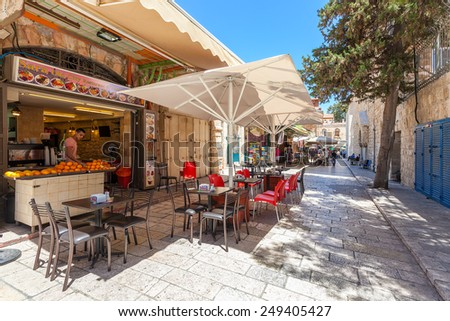 JERUSALEM, ISRAEL - JULY 10, 2014: Typical outdoor restaurant in Muristan neighborhood in Old City  - famous and popular site with tourists and pilgrims visiting Jerusalem. - stock photo