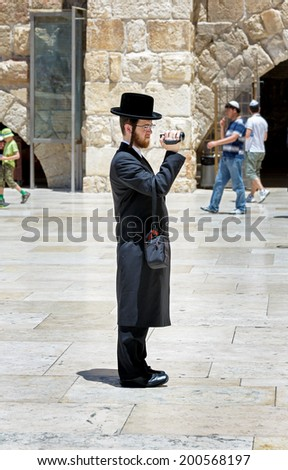 JERUSALEM, ISRAEL - MAY 26, 2013: A Jew makes photo in the holy place. The Western Wall is the most sacred sites in Judaism, it attracts thousands of devotees every day in Jerusalem - stock photo
