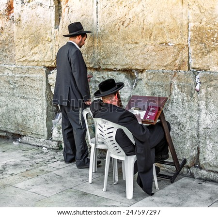 JERUSALEM, ISRAEL - MAY 26, 2013: Jews pray at the holy site. The Western Wall is the most sacred sites in Judaism, it attracts thousands of devotees every day in Jerusalem - stock photo