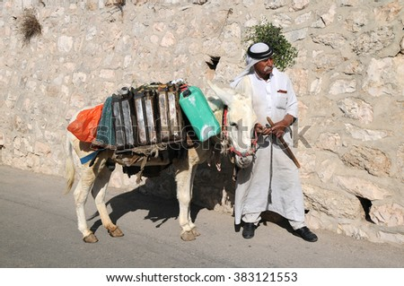 JERUSALEM, ISRAEL - NOVEMBER 10, 2010 Arab man in national clothes and his donkey walk down the hill - stock photo
