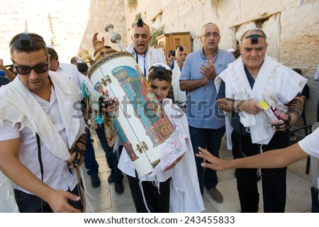 JERUSALEM, ISRAEL - OCT 06, 2014: A 13 years old boy is carrying a torah scroll during a Bar Mitzvah ritual at the Wailing wall in Jerusalem.  - stock photo