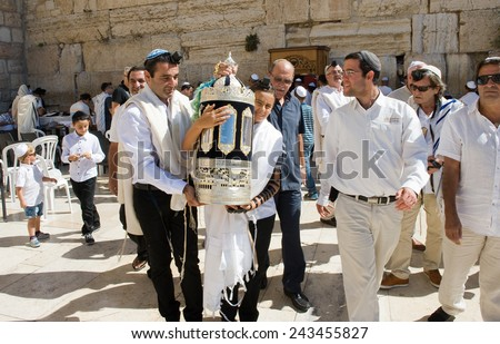 JERUSALEM, ISRAEL - OCT 06, 2014: Bar Mitzvah ritual at the Wailing wall in Jerusalem. A 13 years old boy who has become Bar Mitzvah is morally and ethically responsible for his decisions and actions - stock photo
