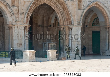 JERUSALEM, ISRAEL - OCT 08, 2014: Israeli military police officers running in front of the Al-aqsa mosque on the temple-square in Jerusalem during fightings with muslims, October 08 in Israel - stock photo