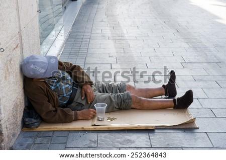 JERUSALEM, ISRAEL - 08 OCTOBER, 2014: A homeless beggar lying on a street in Jerusalem - stock photo