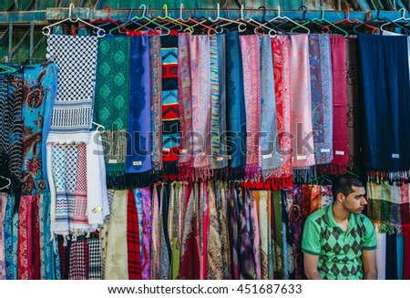 Jerusalem, Israel - October 22, 2015. Man sells textiles on Arab baazar located inside the walls of the Old City of Jerusalem - stock photo