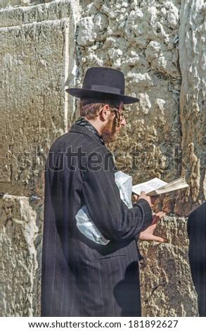 JERUSALEM - JANUARY 1:- Orthodox jewish man prays at the Western Wall on Jan 1, 1994 in Jerusalem, Israel. Israel's annexation of East Jerusalem in 1967 was never internationally recognized. - stock photo