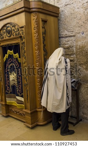 JERUSALEM - JULY 29 : Jewish man prays in the Wailing wall during the Jewish holy day of Tisha B'av, on July 29, 2012 in old Jerusalem, Israel - stock photo