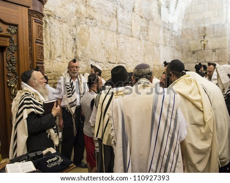JERUSALEM - JULY 29: Jewish men prays in the Wailing wall during the Jewish holy day of Tisha B'av, on July 29, 2012 in old Jerusalem, Israel - stock photo