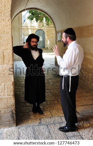 JERUSALEM - JULY 28:Orthodox Jewish men at the Jewish quarter on July 28 2009 Jerusalem,Israel.The quarter is inhabited by around 2,000 residents and is home to numerous yeshivas and synagogues. - stock photo